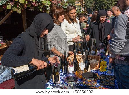 TBILISI, GEORGIA - OCT 16, 2016: Elderly nun woman pours red wine made in the convent during festival Tbilisoba on October 16, 2016. Tbilisoba is traditional festival in capital of Georgia from 1979