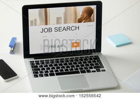 Open laptop on the office desk, job search title on the screen, close up. Human resources, HR concept photo