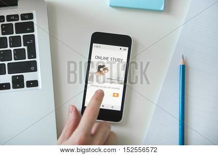 White office desk with a hand touching a mobile phone with a title online study on it. Top view. Education, business concept photo