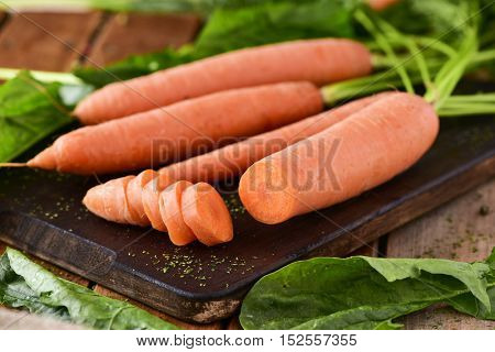 closeup of some raw carrots on a wooden chopping board, on a rustic wooden table