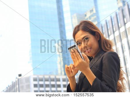 Portrait of Asian business woman on black dress use moblie selfie herself with tower background