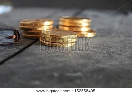 Golden coins and a book on the old vintage wooden table.