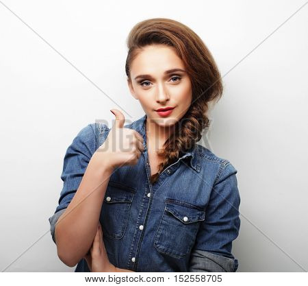 Happy young woman giving thumb up
