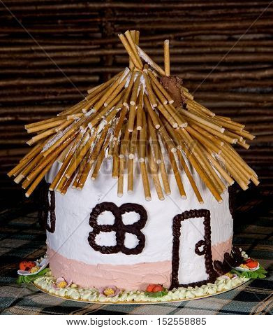 Cake in the form of a house adorned with baked straw flowers from the biscuit and meringue background