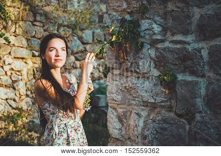 Feminine portrait of young romantic woman with long hair, red lips and manicure in white dress flowers. Pretty female in Stari Bar old fortress, Montenegro. Brunette girl walks around castle