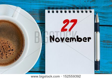 November 27th. Day 27 of month, calendar and white coffee cup at college professor workplace background. Autumn time. Empty space for text.
