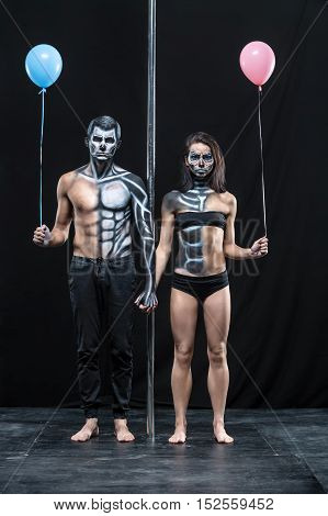 Nice couple of pole dancers holds their hands together next to a pylon on a dark background in the studio. They have body-art and wears black clothes. Girl and guy hold blue and pink balloons.