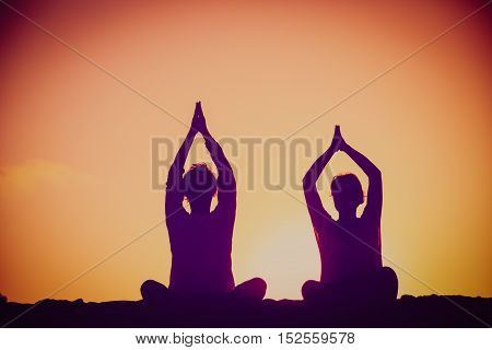 silhouette of couple doing yoga at sunset sky