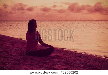 Woman meditation on the beach at sunset