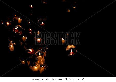 Candles at night in memory of the sorrowful event. Dark background.