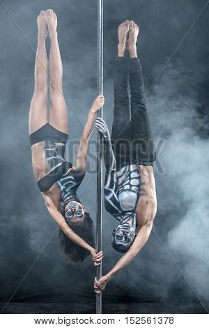 Image of the couple of pole dancers with a horrific body-art in the dark studio with a cloud of a smoke. They are hanging upside down on a pylon and looking into the camera. Vertical.