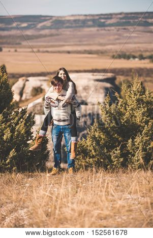 young beautiful loving couple in hipster fashion style posing on mountain. outdoor close up portrait