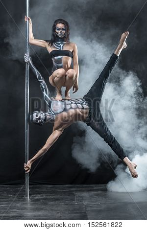 Cool couple of pole dancers with a horrific body-art in the dark studio with a cloud of a smoke. Man with outstreched arms and legs holds a pylon and hangs in the air. Girl sits on his torso. Vertical.