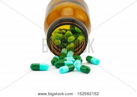 Antibiotic capsule and a bottle on white background