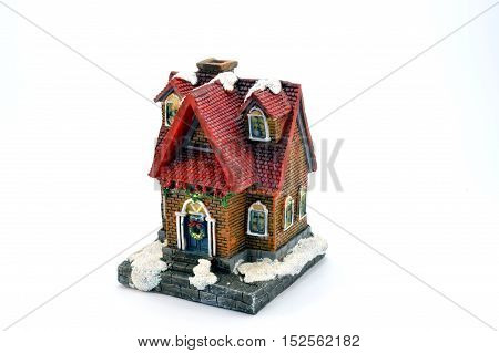 Small plastic house under the snow with a red roof in tiles