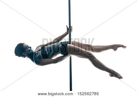 Smiling pole dancer with a body-art hangs horizontal with stretched legs on a pylon in the studio on the white background. She wears black sport underwear and holds her hands on the pylon. Horizontal.