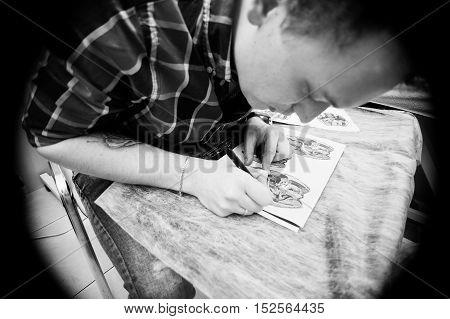 Tattoo Master Preparing Sketch For Tattoo. Vignette Effect Photo