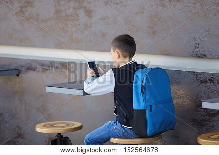schoolboy using smartphone in cafe city street