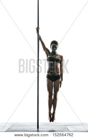 Athletic pole dancer with a body-art hangs in the air in a studio on a white background. She holds a pylon with the right hand. Girl wears black sport underwear. Vertical.