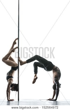 Athletic couple of pole dancers with horrific body-art stands on their hands upside down next to a pylon in the studio on the white background. They are using the pylon like a fulcrum. Vertical.