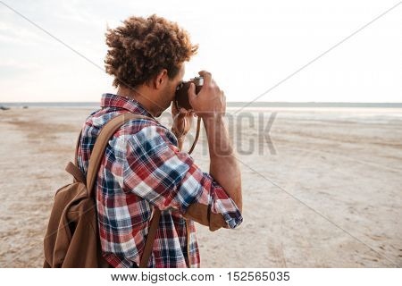 Curly african american young man with backpack standing and taking pictures on the beach