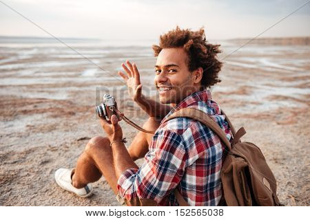 Cheerful african young man with backpack taking pictures with old vintage camera on the beach