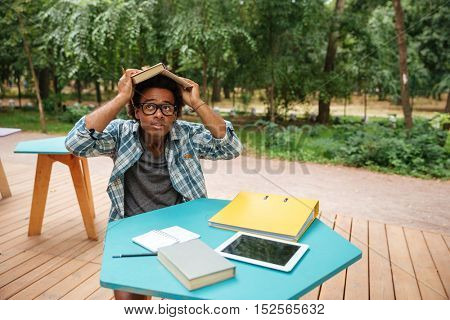Funny playful young man with book on head sitting in outdoor cafe