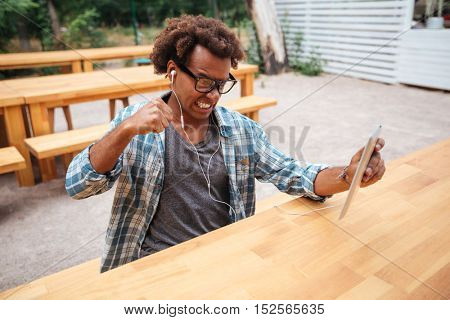 Mad irritated african young man in glasses and earphones using tablet in outdoor cafe