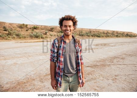 Happy african american young man with backpack standing outdoors