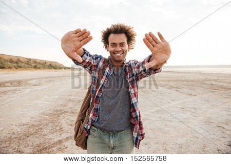 Cheerful african man with backpack focusing by his hands on the beach