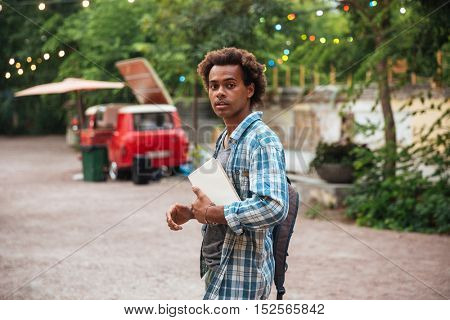 Attractive african young man with backpack and books walking in the park
