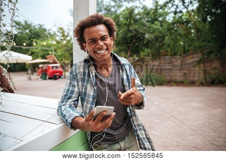 Cheerful african young man listening to music from mobile phone and laughing