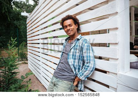 Portrait of happy handsome african young man standing outdoors