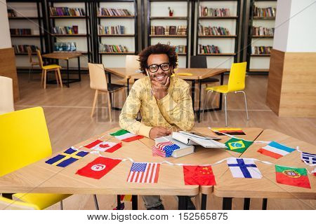 Cheerful african young man sitting at the table with books and flags of countries in library