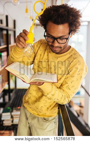 Concentrated african young man holding light bulb and reading a book in library