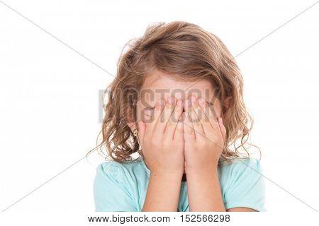 Little girl keeps her eyes shut. All on white background.