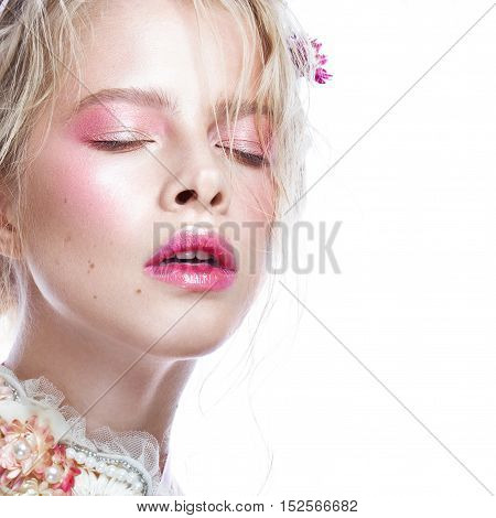 Beautiful blond fashion girl with flowers on the neck and in her hair, wet Nude makeup. Beauty face. Photos shot in the studio.