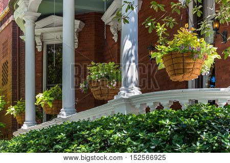 Several flower baskets with foliage hanging from a porch with white pillar columns on a brick house.