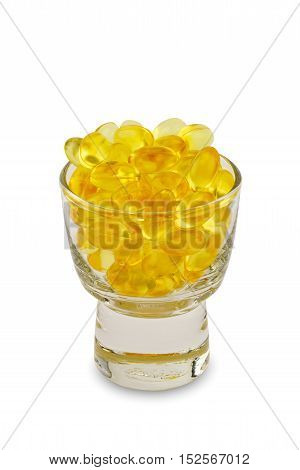 Capsule of medicine in a small glass on white background