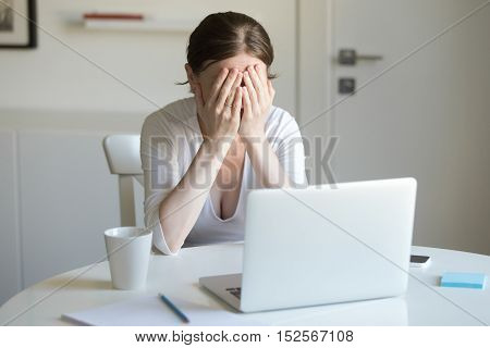Portrait Of Woman At The Desk With Laptop, Hands Closing Face