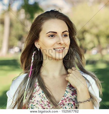 Portrait of beautiful happy caucasian girl with braces in the nature background. Healthcare concept.