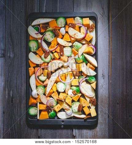 Roasted vegetables on a baking sheet: sweet potato, butternut squash, brussels sprouts, apple, pecans and pear. Toning. Healthy eating concept.