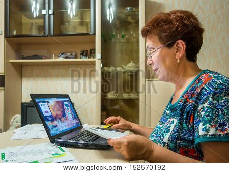 Voronezh, Russia - June 19, 2016: Elderly a smiling woman uses the online system of the bank to pay the bills