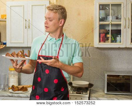 happy young pastry chef, a man proudly holds cooked pie.