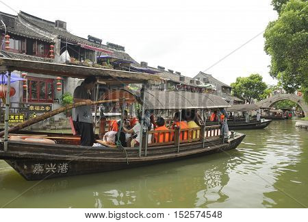 August 8 2015. Xitang Town China. Tourist boats on the water canals of Xitang Town in Zhejiang Province China on an overcast day.
