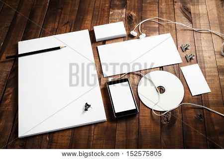 Photo of blank paperwork template. Responsive design mock up on wooden table background. Template for branding identity. Stationery set.