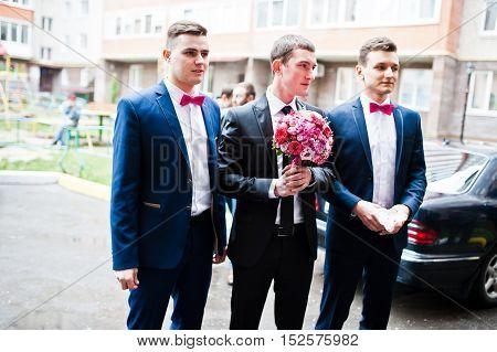 Groom with groomsman background wedding cars at wedding
