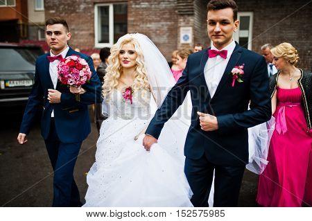 Stylish groomsmen walking with bride at wedding