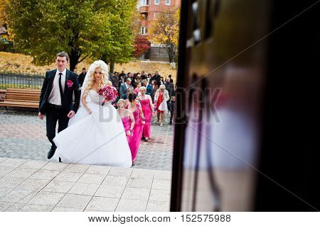 Stylish wedding couple enter the church with guests