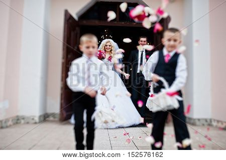 Wedding couple out from church registration children strew petals of roses